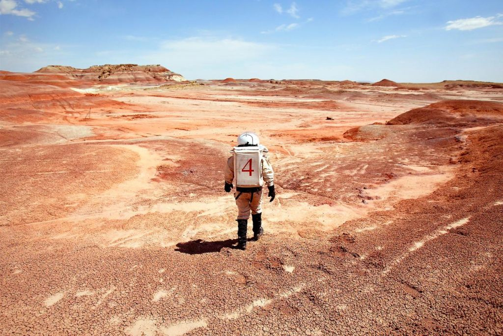 一名穿著太空衣的科學家走在位於猶他州漢克斯維爾(Hanksville)的火星沙漠科學研究站(the Mars Desert Research Station)附近。該地地貌和火星地表相似,因此被科學家們選為測試技術和裝備的地點。PHOTOGRAPH BY DAVID HOWELLS, CORBIS/GETTY IMAGES