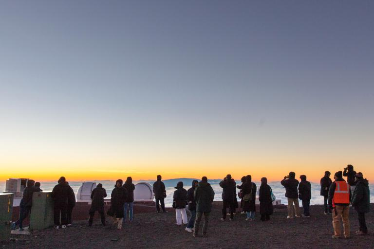 遊客在茂納開亞火山(Mauna Kea Volcano)的雲海之上欣賞日落。PHOTOGRAPH BY CURVED LIGHT USA/ALAMY
