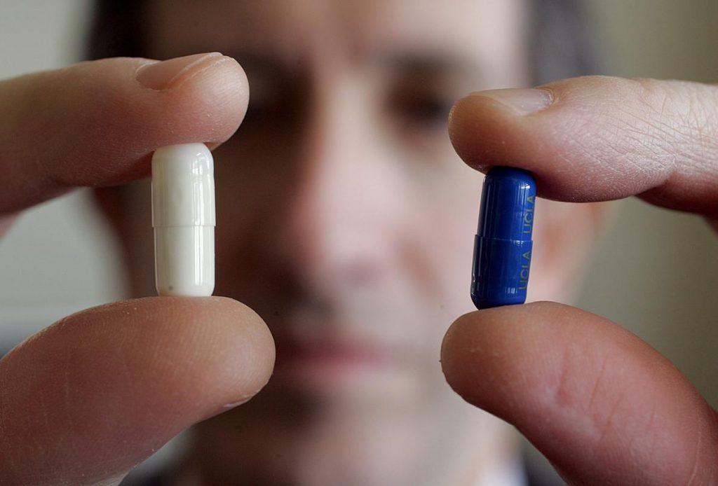 精神病醫師安德魯‧路卻特(Andrew Leuchter)拿著兩個膠囊——其中一顆是藥物,另一顆則是安慰劑。病人並不知道哪個是哪個,但其實這兩者都能提供有效治療。PHOTOGRAPH BY SPENCER WEINER, LOS ANGELES TIMES/GETTY IMAGES
