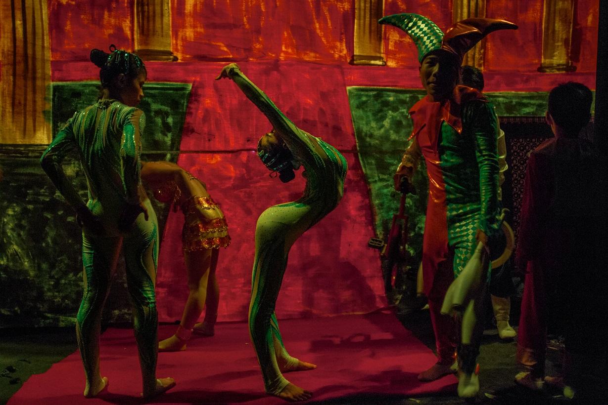 阮氏(中)在胡志明市演出前進行暖身運動。越南的馬戲團藝人一個月的收入大約是150美元,每次演出還有四美元的額外補貼。這樣的收入不足以維生,所以多數藝人會在私人宴會上或夜總會裡表演賺外快。Photograph by Christian Rodriguez
