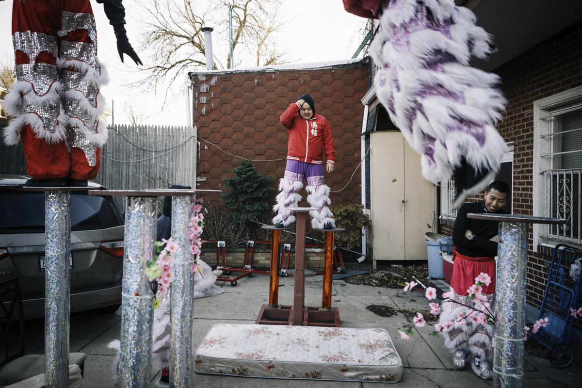 溫富璋(中)和陳子強(右)在紐約皇后區一間住家後院練習高樁上的步法,地上鋪的舊床墊是為了防止失足摔傷。