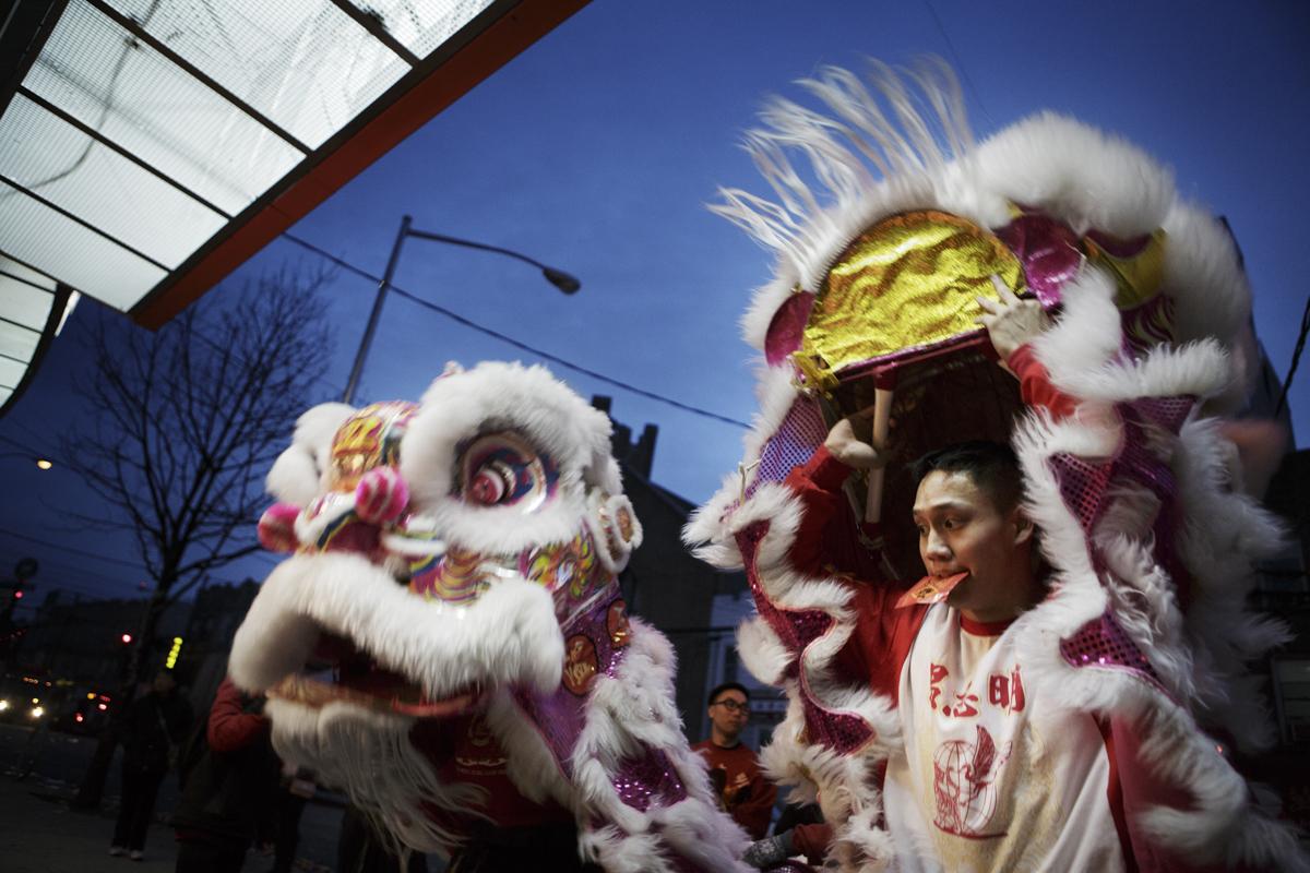 劉卓鋒(Eric Lau)啣著布魯克林一間店家發的紅包,一邊和搭擋向商家回禮。過年時商家店主都會贈送舞獅團紅包。