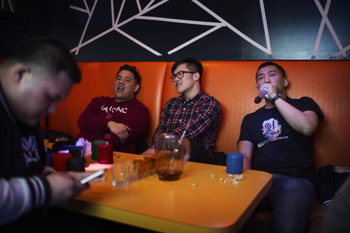 溫志明龍獅團團員在紐約布魯克林一間KTV幫一位團員慶生,陳子強(右一)、伍俊匡(右二)引吭高歌,黃日威(左一)忙著玩手機。