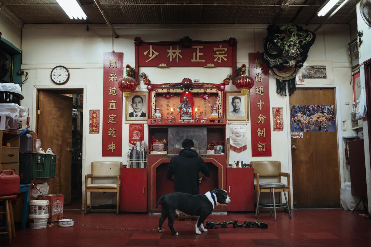 張琦峰(Vincent Chong)跪在溫志明洪拳國術總會的神桌前低頭祝禱。每當有新成員要加入溫團,第一次進門時,都得遵照這項傳統向溫團師祖和神明上香,才能正式拜入門下。掌門人溫志明年少時向香港的陸智夫(供奉於神壇左方)學習舞獅和白鶴拳,洪拳功夫則師承父親溫柏良(供奉在神壇右方),兩旁對聯寫的是洪拳十二橋手訣。