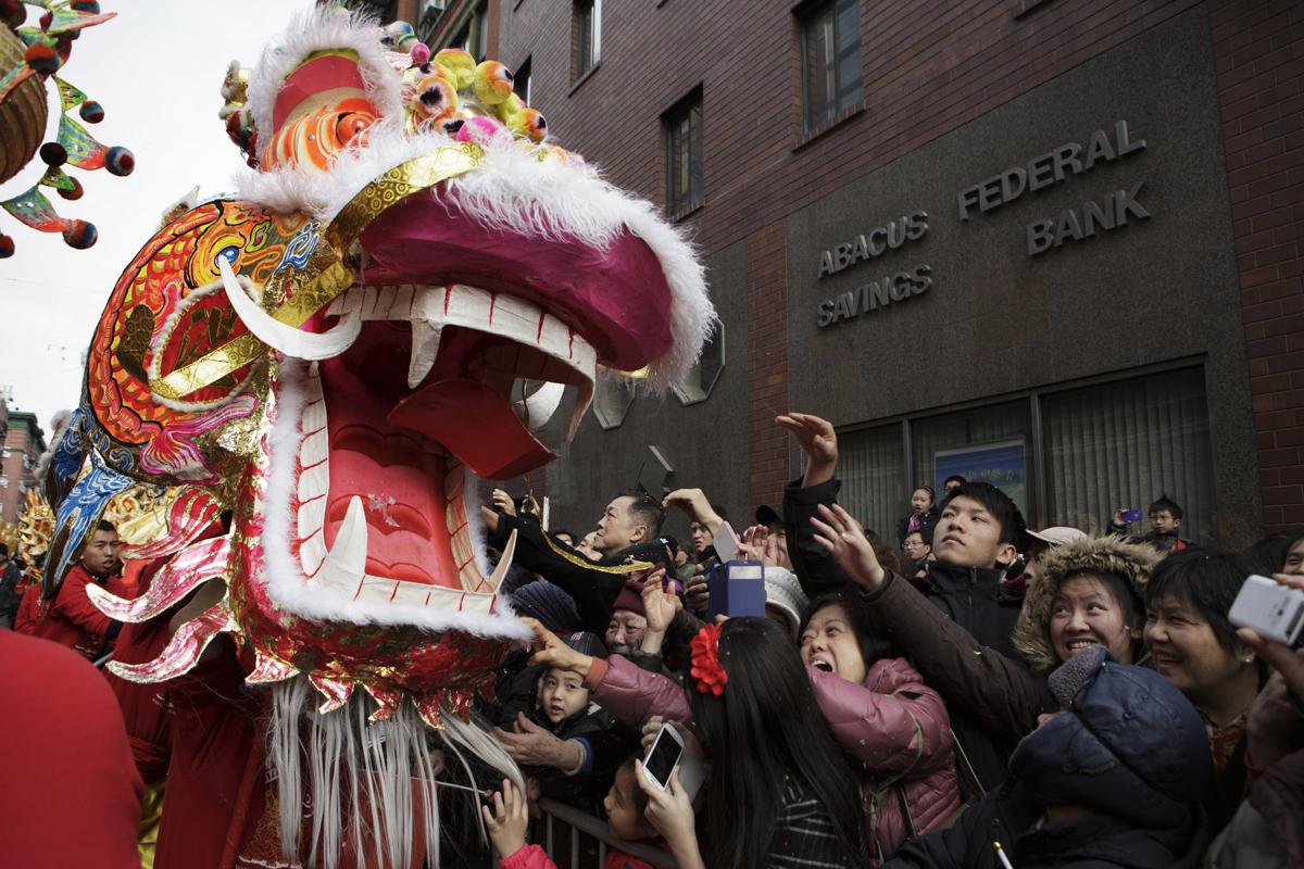 紐約農曆新年遊行時,溫志明龍獅會舞出大型金龍,圍觀民眾爭相搶摸龍頭,希望帶來好運。