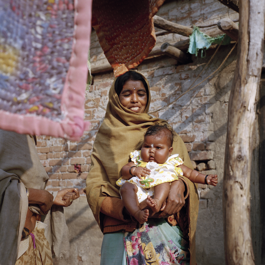 "Dec. 20 2016 - Nanpatiya Kumar, 41 plays with Jyoti, her neighbor's baby in the village of Kolodohar, Jharkhand. Nanpatiya lost her husband 3 years ago due to breathing problems as she could not afford a doctor. ""If my husband would have been here I wouldn't worry so much, now I worry about the kids all the time. How will I get them married?"" Despite Nanpatiya's challenges, the women of Kolodohar have found comfort in one another with many of the men migrating for work to other states."